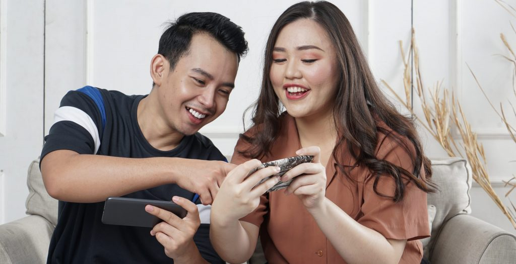 Image of excited young man and woman playing together and competing in video games on smartphones